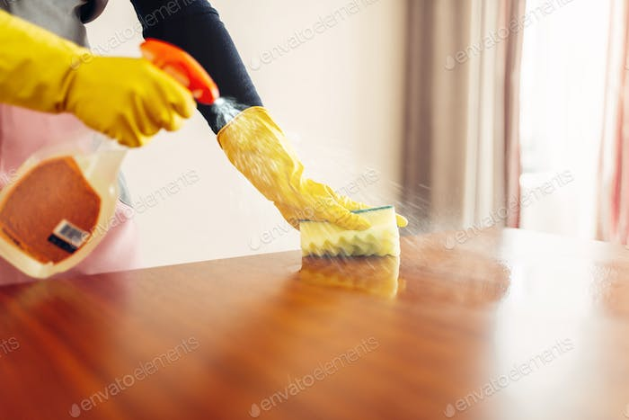 Housemaid hands cleans table with cleaning spray