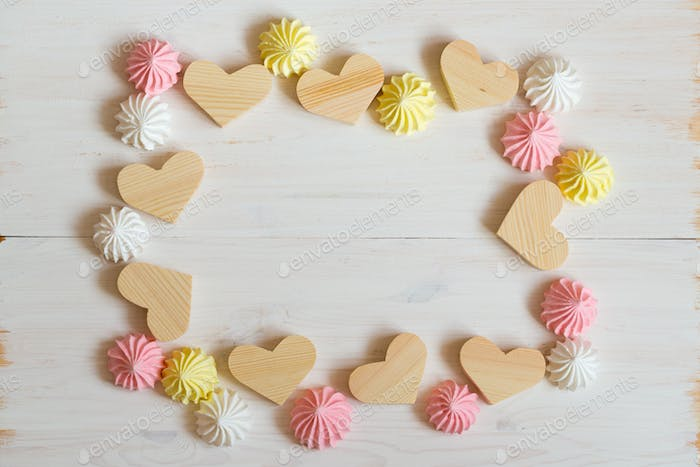 Frame made of wooden hearts and meringue pastel colors on a whit