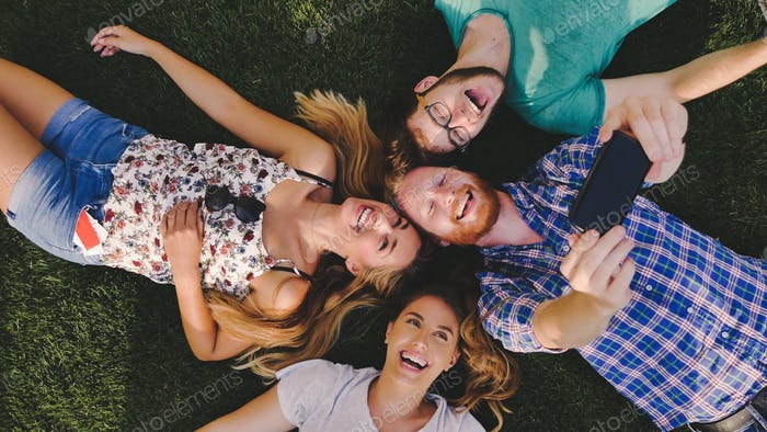 Careless young people having a laugh outdoors lying in grass
