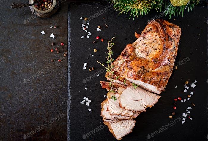 Gebratener, in Scheiben geschnittener Weihnachtsschinken aus Truthahn auf dunklem rustikalem Hintergrund. Draufsicht. Festivalessen.