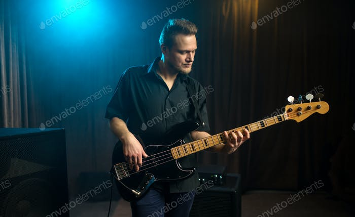 Male guitarist playing an electric bass guitar