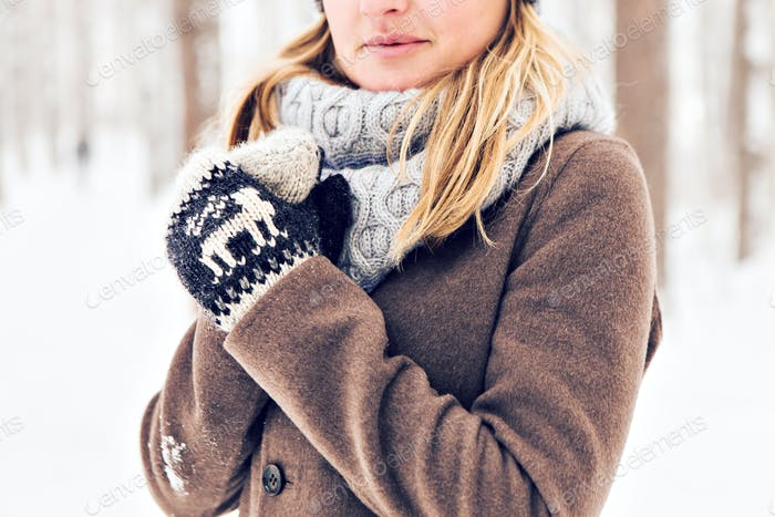 Closeup of young woman in wintertime outdoor. Snow and cold