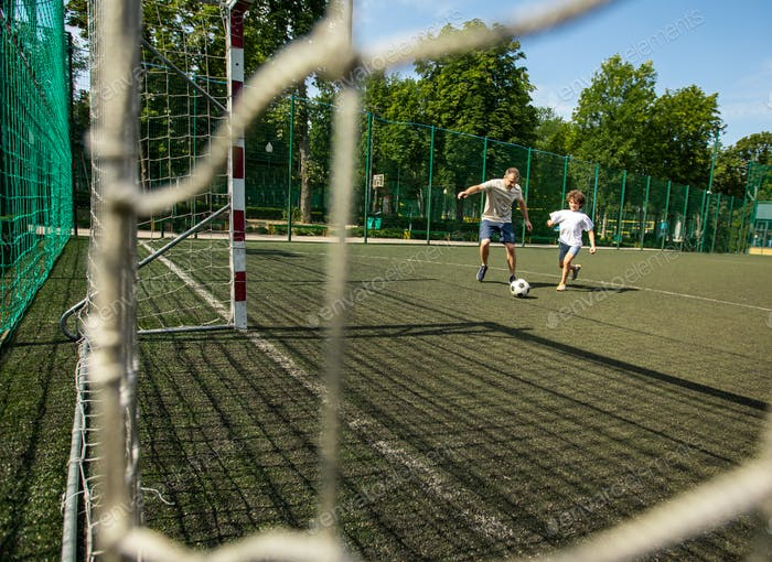 Sportlicher Mann spielt Fußball mit kleinen Jungen
