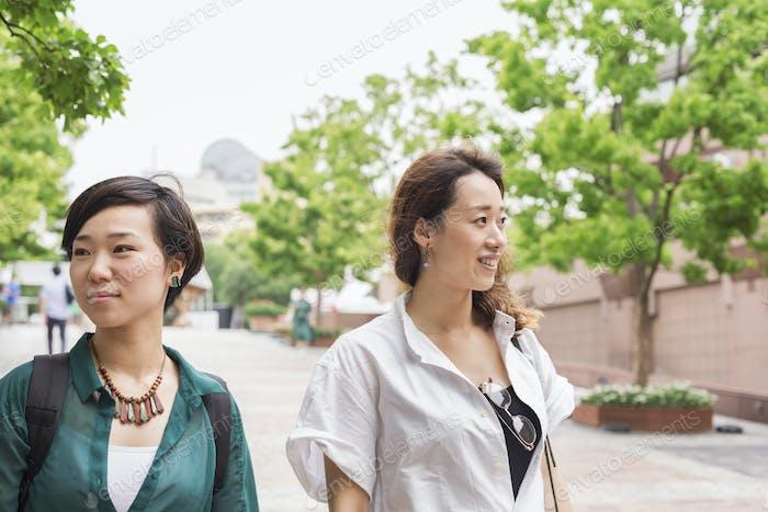 Two women with black hair wearing white and green shirt walking along street, smiling.