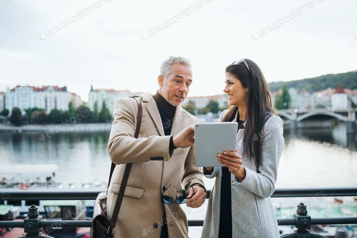 Man and woman business partners with tablet standing by a river in city of Prague.