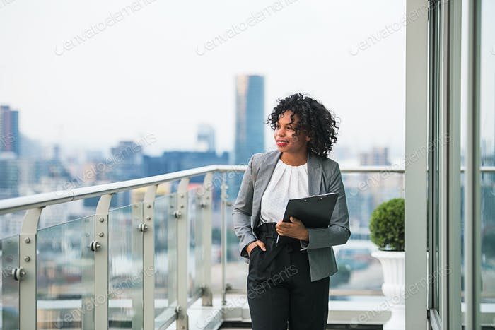 A portrait of a businesswoman with clipboard walking on a terrace.