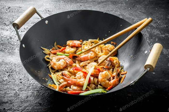 Hot Chinese wok Udon noodles with sauce, shrimp and vegetables.
