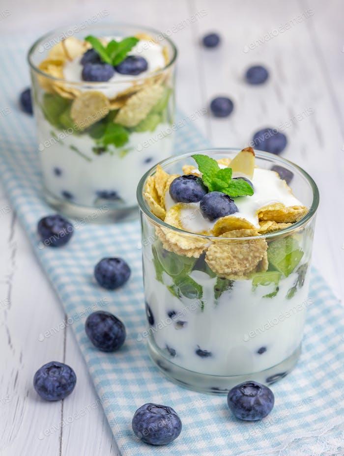 Joghurt-Dessert mit Heidelbeere, Kiwi und Getreide im Glas auf dem Tuch