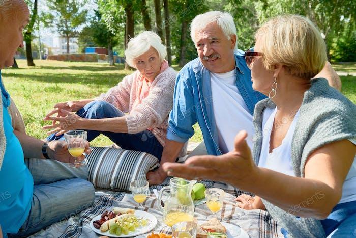 Seniors Enjoying Picnic in Sunny Park