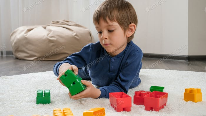 Lindo niño acostado en una alfombra suave y jugando con bloques de juguete de colores. Concepto de niño