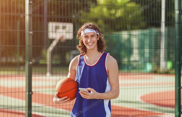 Happy millennial basketball player with mobile phone at outdoor court