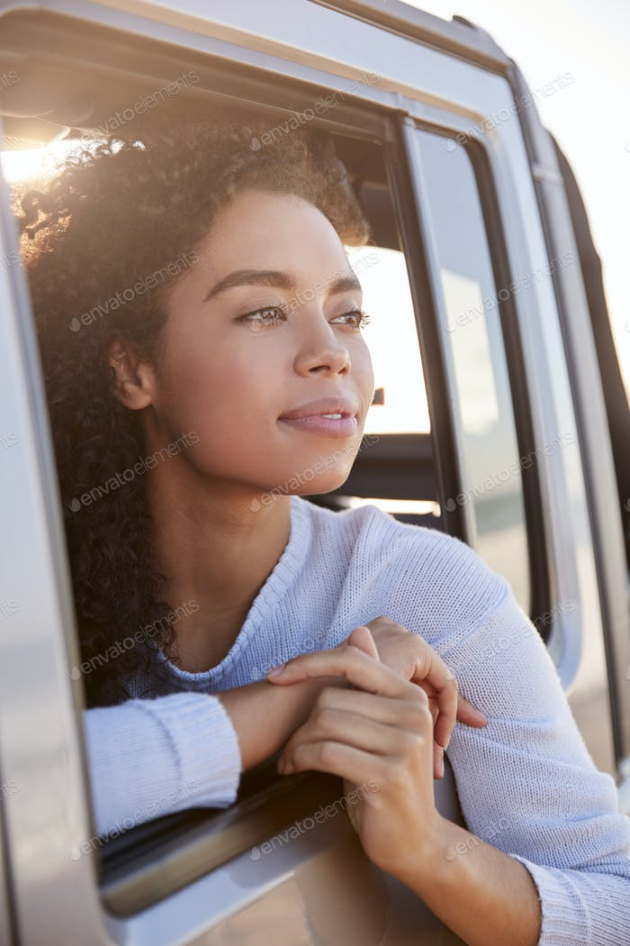 Woman looking out of front passenger car window, vertical