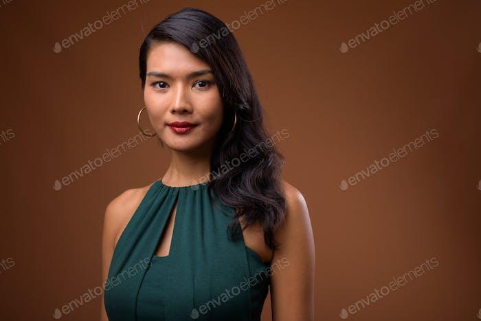 Studio shot of beautiful Asian businesswoman in green dress
