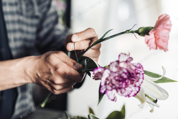 Young male florist working in flower shop