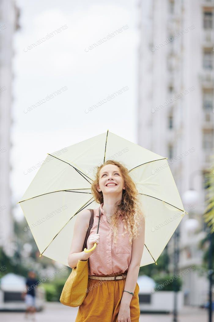 Chica Alegre caminando con paraguas