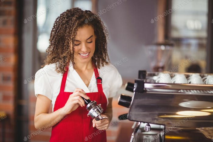 A smiling barista pressing coffee at the coffee shop