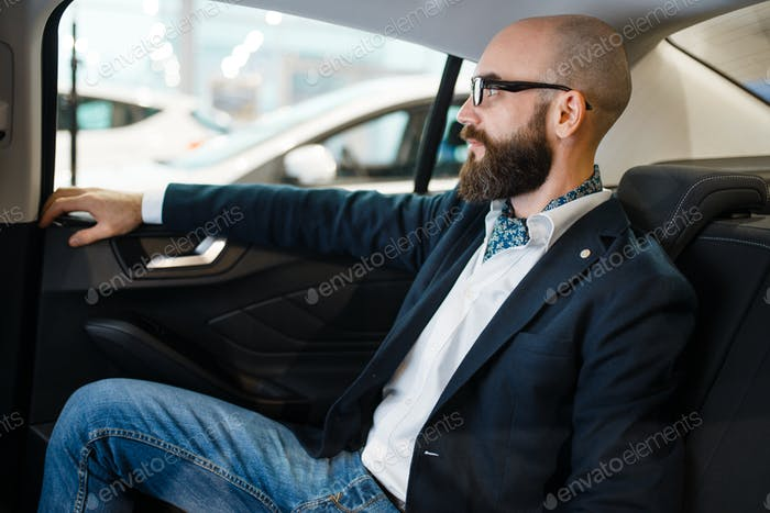 Man checks the comfort of rear seats in automobile