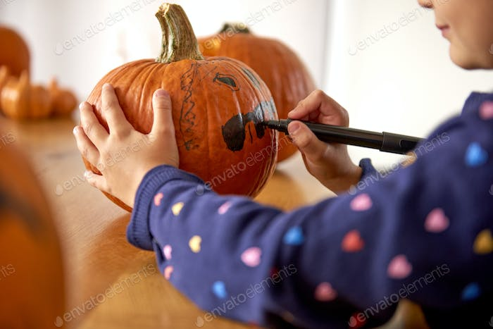 Close up of child drawing on halloween pumpkin