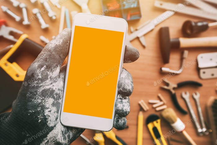 Handyworker smart phone app, repairman holding mobile phone in h