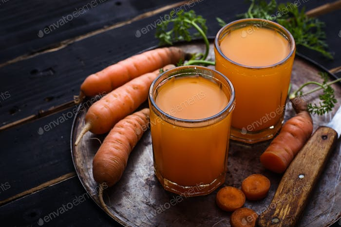 Glasses of carrot juice on black background