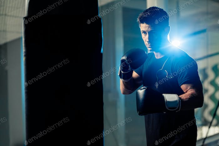 muscular handsome boxing man fighter with boxing bag