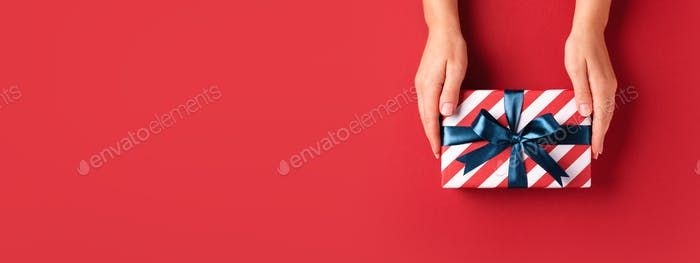 Red Banner with Female's Hands Holding Striped Gift Box.