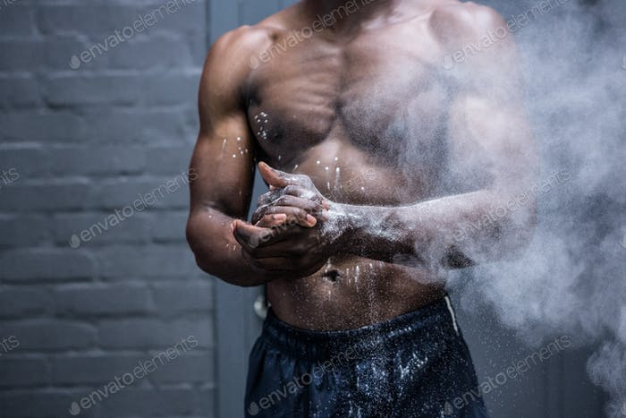 Young Bodybuilder shaking Chalk off his hands in the crossfit gym