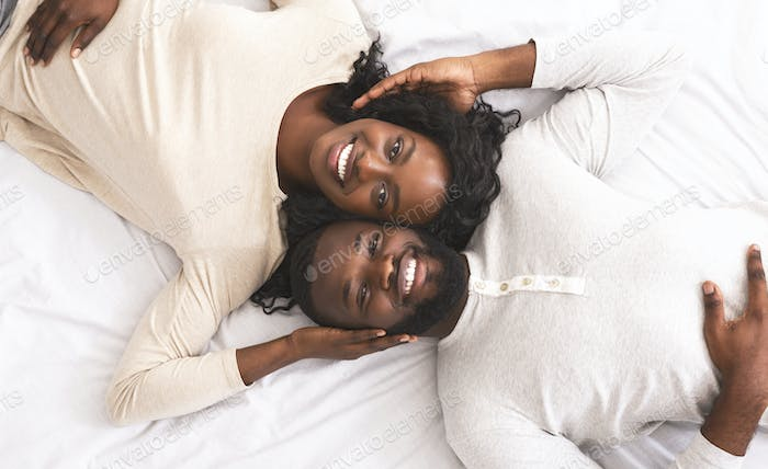 Top view of young black couple lying in bed together