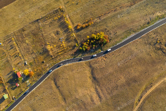 Aerial drone view of winding asphalt road at autumn