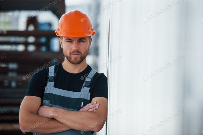 Serious industrial worker indoors in factory. Young technician with orange hard hat