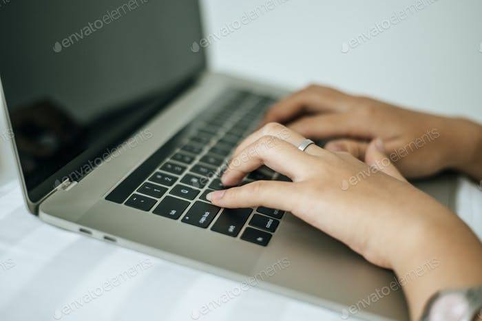 The hand that is put on the laptop.