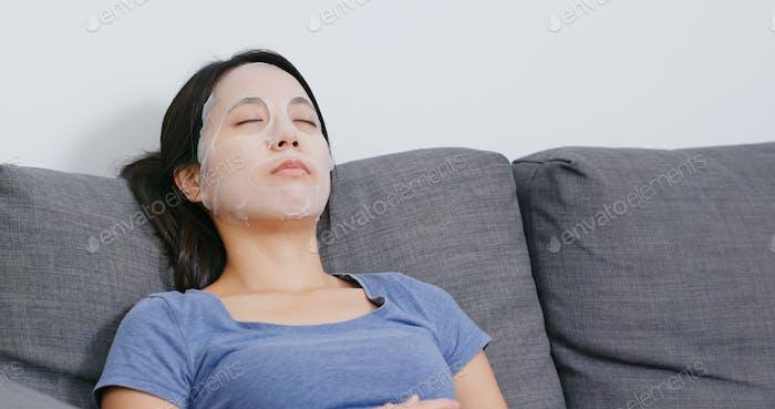 Женщина нанесите маску на лицо и лежа на диване