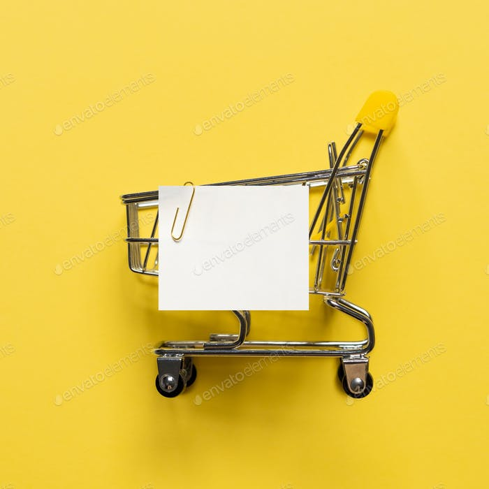 Shopping cart and white paper note list on yellow