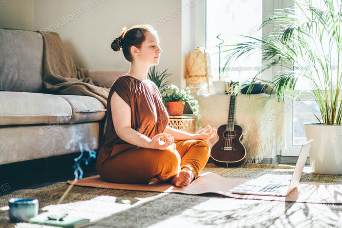 Woman doing yoga and watching tutorial lesson on laptop at home.