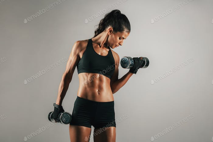 Woman with toned muscular body lifting weights