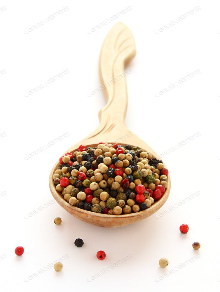 Black, white and red pepper spice on wooden spoon