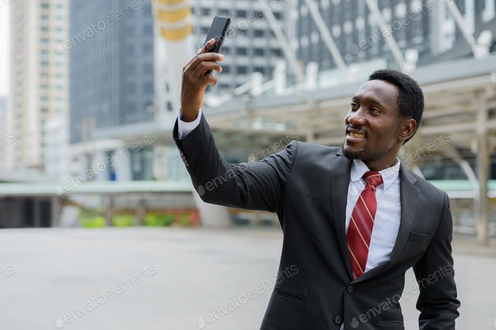 Young happy African businessman taking selfie in front of modern building at Bangkok city