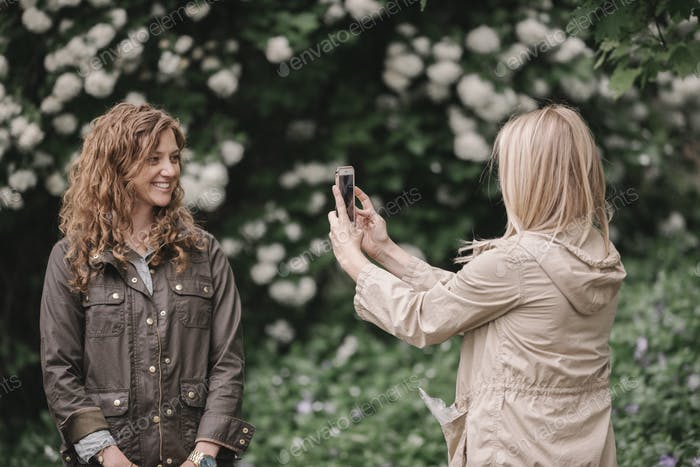 A woman taking a photograph with a smart phone of her companion on a country path.