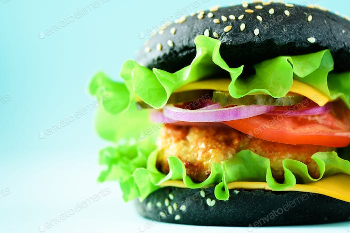 Delicious burger with beef, cheese, lettuce, onion, tomatoes on yellow background. Close up banner