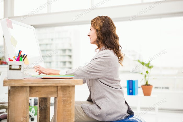 Casual businesswoman sitting on exercise ball while working in the office