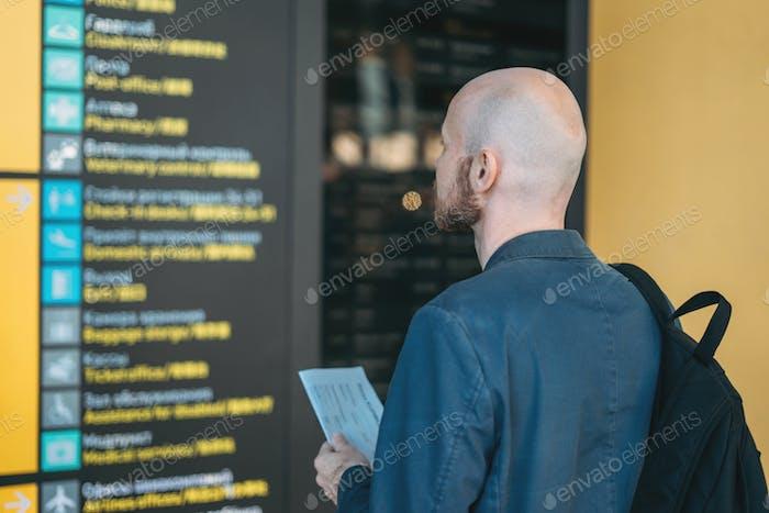 Красивый лысый бородатый мужчина в костюме с рюкзаком читает информацию в аэропорту