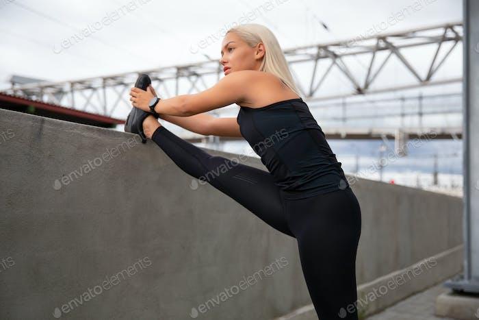 Confident Female Athlete Stretching Leg On Railing At Sidewalk