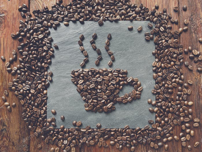 Cup from coffee beans at stone background