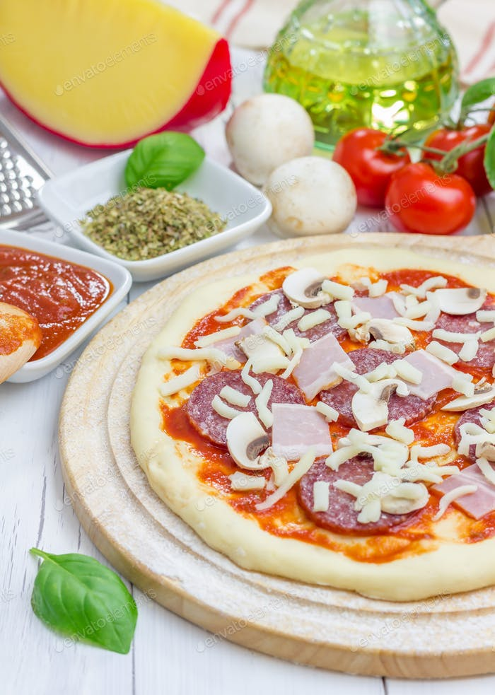 Pizzateig mit Salami, Speck, Pilzen und Käse