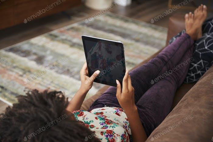 Woman Lying On Sofa At Home Using Digital Tablet