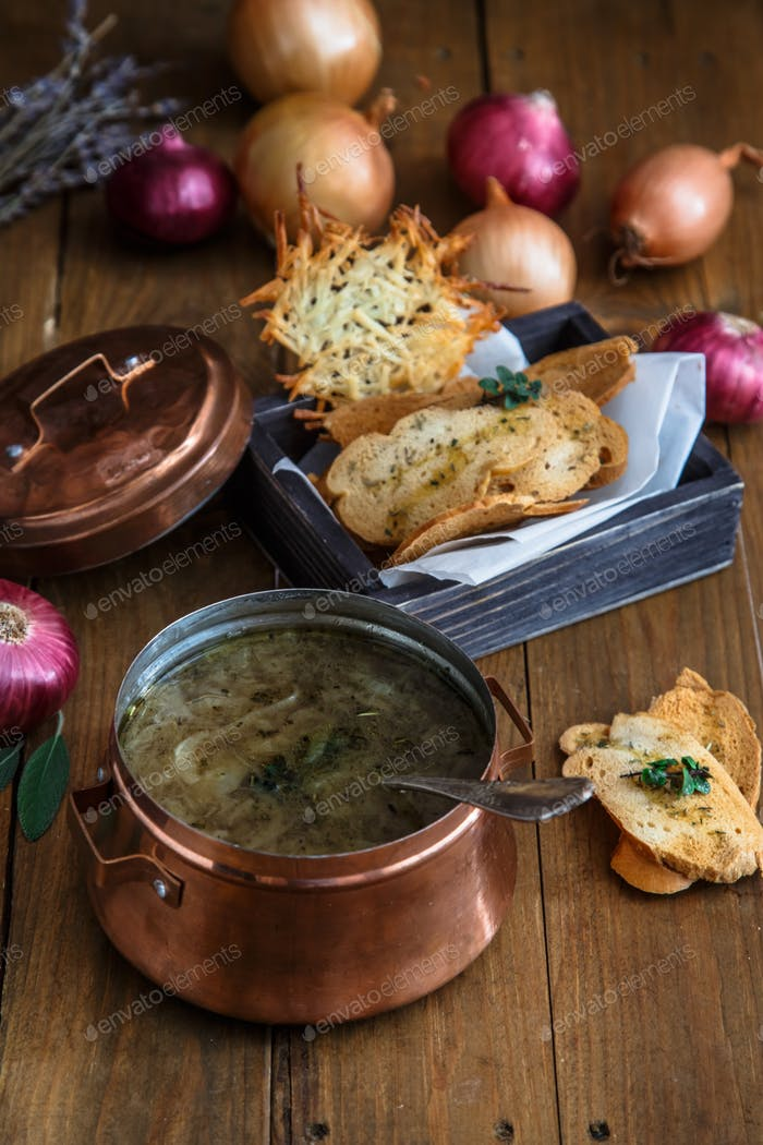 Traditional onion soup with cheese and croutons, colorful onions on background