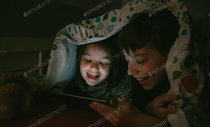 Brothers looking at the tablet in the dark