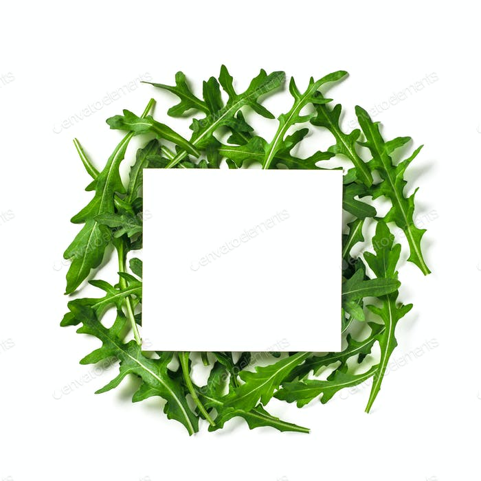 White paper square on heap of arugula