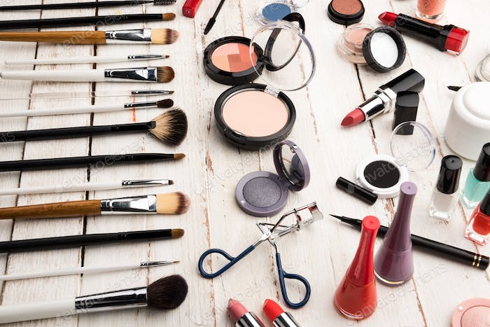 close up view of various brushes and cosmetics for applying makeup on table