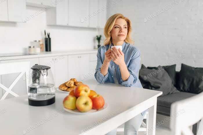 Woman drinks coffee with milk on the kitchen